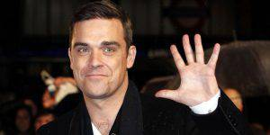 British singer Robbie Williams gestures as he arrives at the 30th Brit Awards ceremony at Earl's Court in London