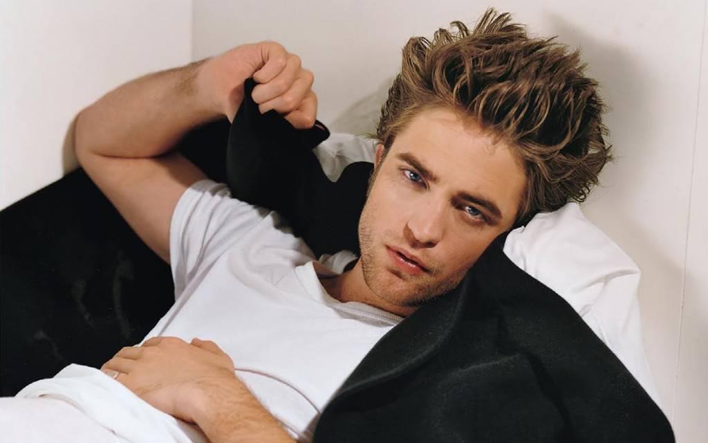 uomo disteso su letto con capelli scompigliati e sguardo sexy