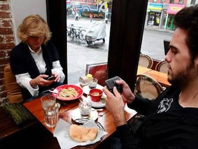 un uomo e una donna a tavola, entrambi impegnati ad usare il proprio smatrphone