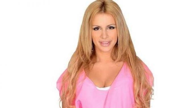 ragazza bionda e prosperosa con capelli lunghi indossa abito rosa con scollatura