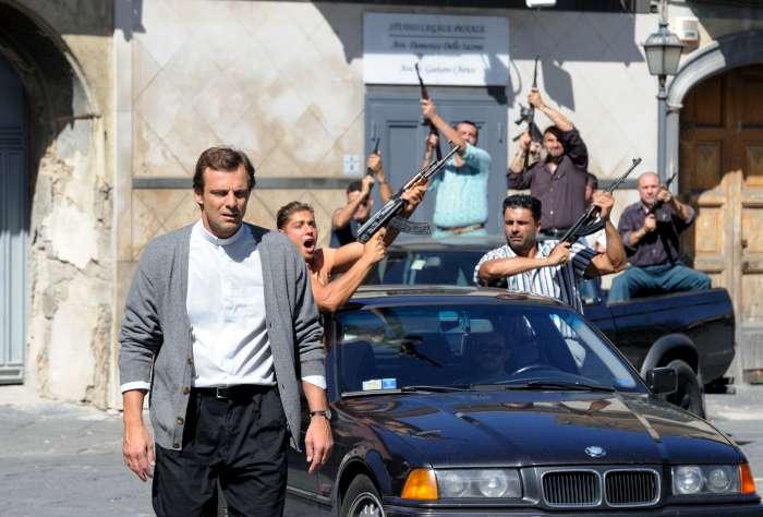un prete cammina dietro una macchina piena di uomini con fucili